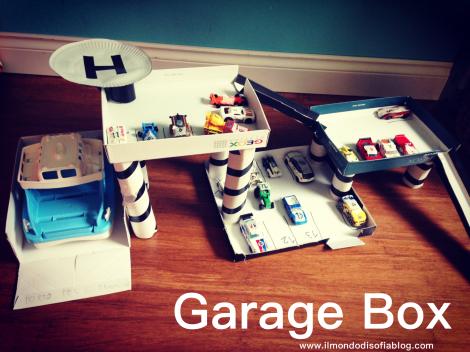 garage costruito con le scatole da scarpe e i coperchi e cpon i rotoli della carta igienica e dello scottex